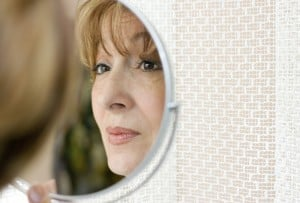 Mature woman looking at her face in the mirror