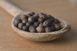 allspice grain in spoon on wooden background