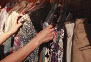 A woman is browsing a rail of clothes in a charity shop