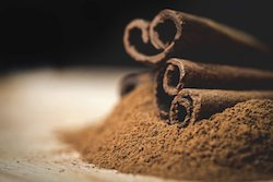 Cinnamon sticks with cinnamon powder on wooden background