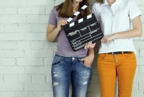 Two women holding a clapboard against brick wall with copy-space