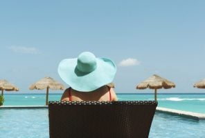 Woman in a blue hat sitting on a sun lounger looking at an empty pool