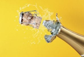 Neck of a champagne bottle and cork popping, against a yellow background