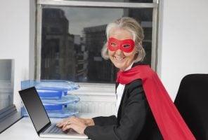 Portrait of senior businesswoman in superhero costume using laptop at office desk