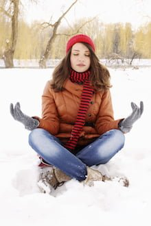 Woman in a lotus position on the snow