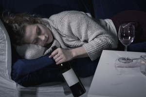 Tired drunk woman sleeping with bottle of wine