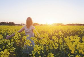 Woman enjoing summer in yellow field at sunset