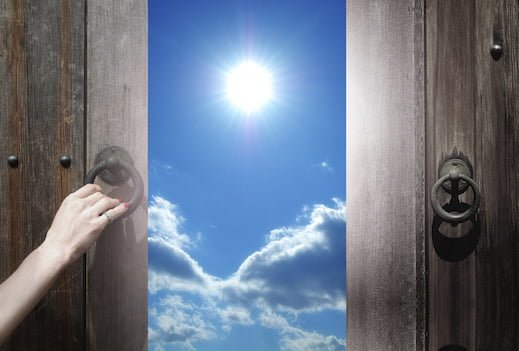 Woman opening two wooden doors to a blue sky with bright sun