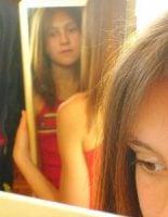 teenage girl reflected in mirror