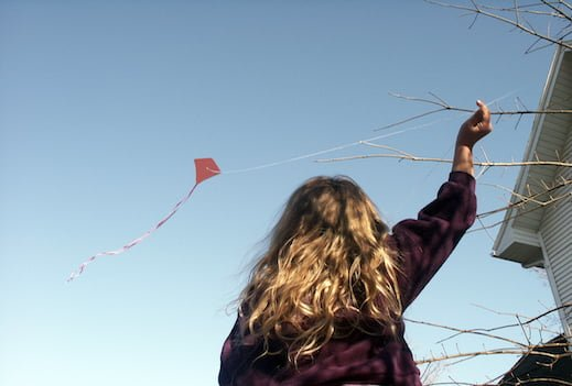 Girl flying a red kite against a blue sky