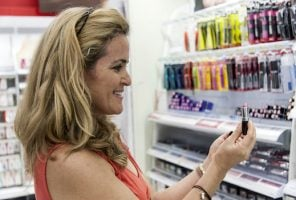 Woman looking at lipstick on a self-selection make-up counter