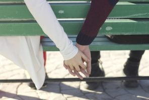 Couple holding hands sitting on a green bench