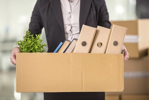 Businesswoman holding cardboard box with her things.