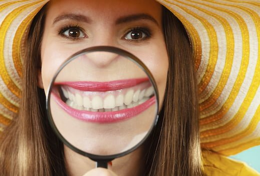 Closeup funny woman in summer hat smiling and show teeth through a magnifying glass