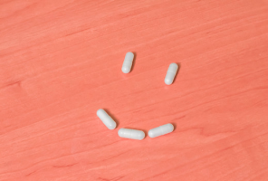 pills arranged in a smiley face on a wooden table