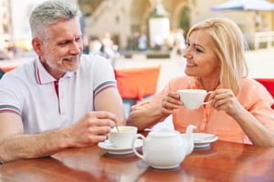 White haired man and older woman having cup of tea and smiling