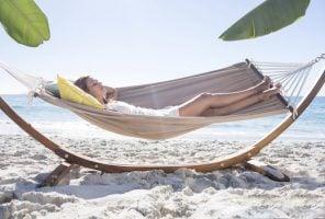 Woman relaxing in a hammock on a sandy beach