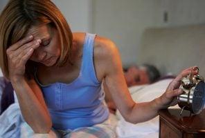 woman on edge of bed unable to sleep