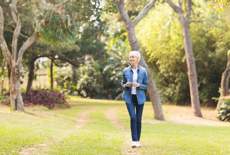 relaxed middle aged woman walking at the park