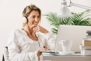 Lady working on laptop wearing headphones