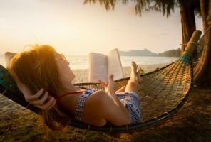 woman relaxing on hammock with book
