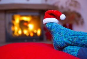 Relaxing at the fireplace on winter evening.Woman relaxes by warm fire and warming up her feet in woollen socks and Santa hat .Winter and Christmas holidays concept.