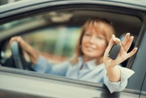 Woman sitting in a car and showing car key.Focus on key.