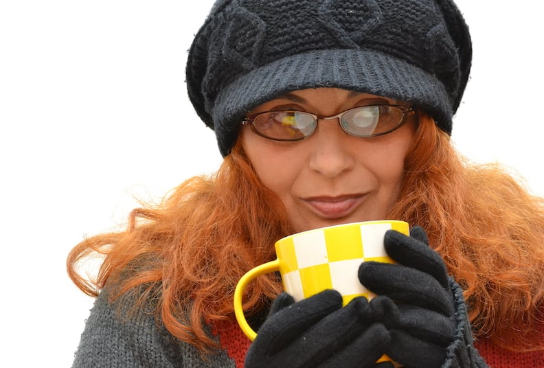 Redhead woman with a black cap and a cup of tea on a white background. Close-up.