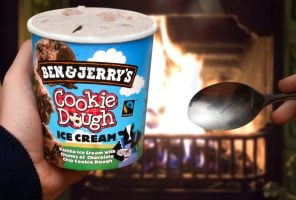 A tub of Ben & Jerry's ice cream being eaten in front of a fireplace