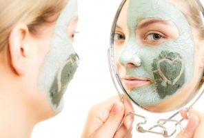 Skin care. Woman in clay mud mask on face with heart on cheek looking in the mirror isolated on white. Girl taking care of dry complexion. Beauty treatment.