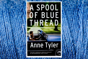 A Spool of Blue Thread book by Anne Tyler with a spool of blue thread in the background