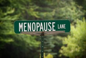 Green street sign with white letters for Menopause Lane. Use it for humor regarding middle age for women.