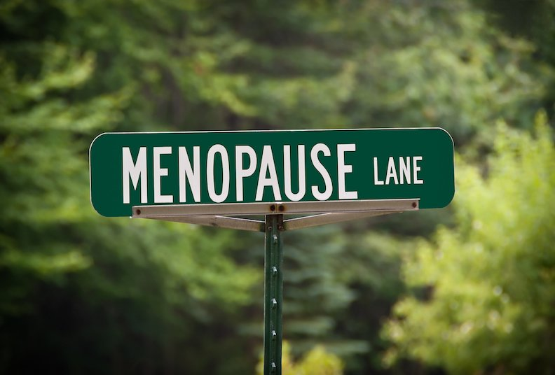 Green street sign with white letters for Menopause Lane.