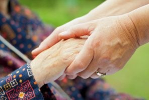 Occupational therapist's hand holding a elderly hand