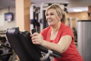 Happy woman riding on exercise bike at the gym