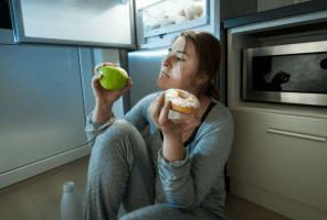 woman sitting by fridge