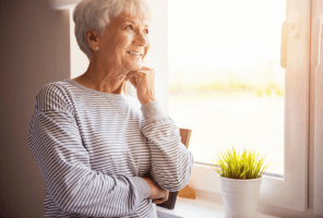 older woman smiling looking through window