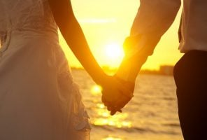 Groom and bride holding hands on beach at sunset