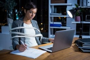 Businesswoman tied with rope while working on laptop at her desk in office at night
