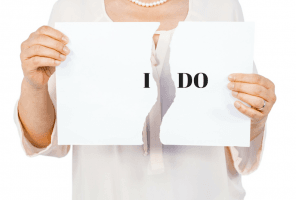 Woman ripping up paper with the words 'I DO' to signal divorce