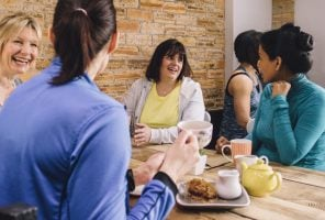 Women are sitting at a table in a cafe, socialising over tea and cake talking about menopause