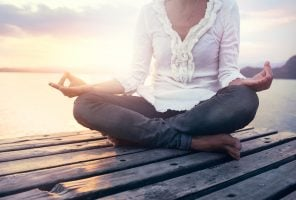 beautiful woman meditating on a boardwalk at sunset