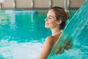Beautiful woman enjoying jet of water in spa  resort