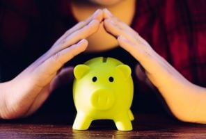 Saving for retirement, woman with hands over piggy bank
