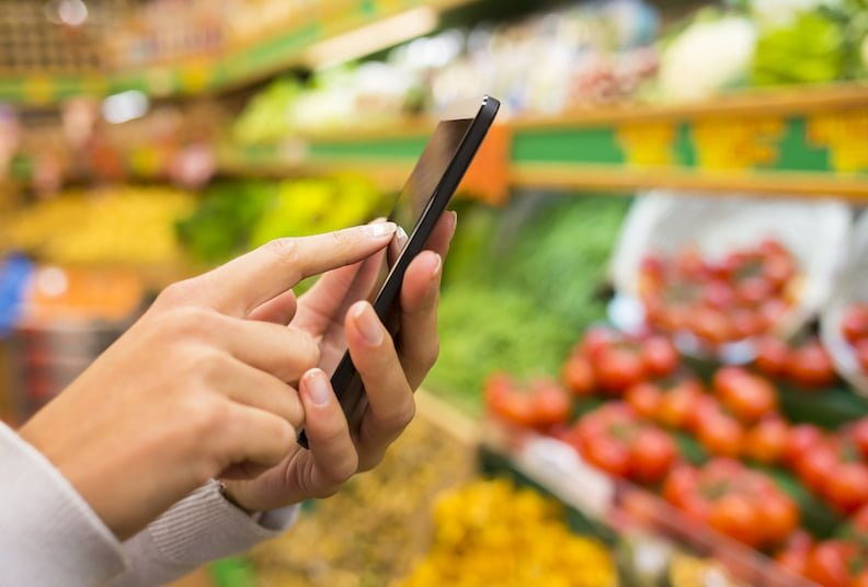 Eating during menopause: woman shopping using iPhone list