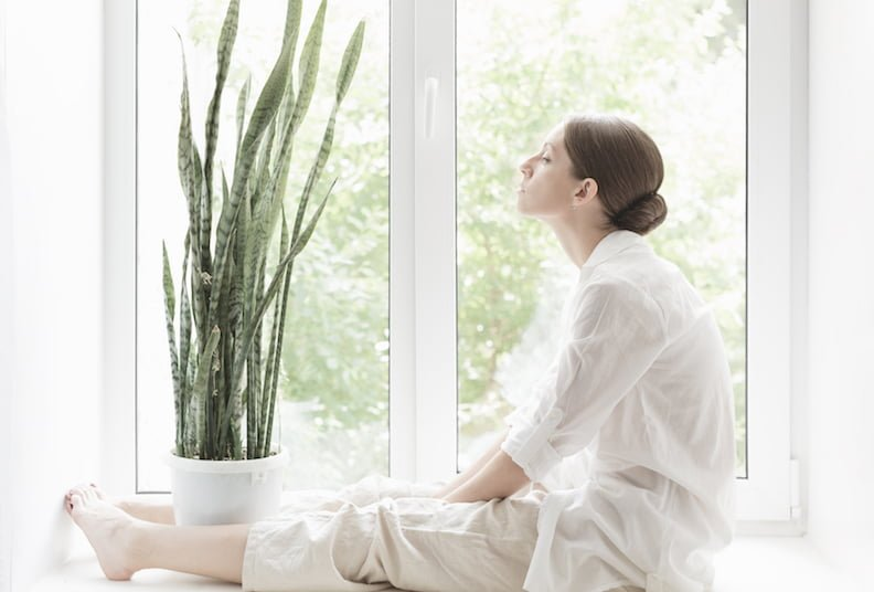 Home environment: woman relaxed at home sitting on the windowsill