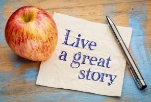 Life concept - live a great story, handwriting on a napkin with a fresh apple