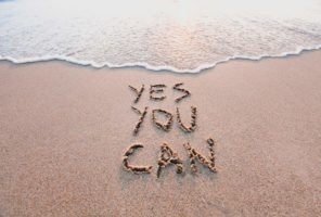 motivational inspirational message 'yes you can' written on a beach