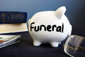 Funeral plan written on a side of piggy bank.