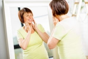 Older woman looking into the mirror